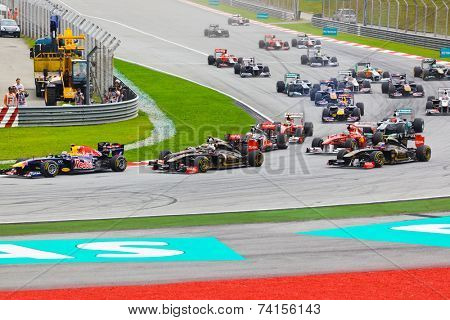 SEPANG, MALAYSIA - APRIL 10: Cars race around the corner on the first lap at the Formula 1 GP, on April 10, 2011 in  Sepang, Malaysia.