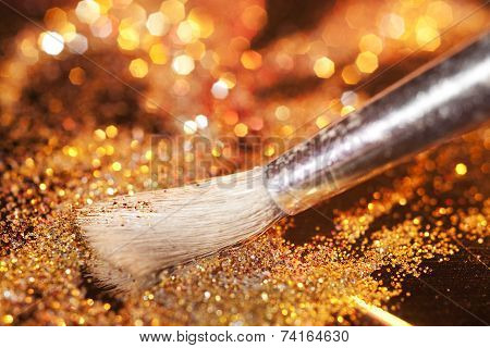 Close-up on makeup brush and gold shining powder