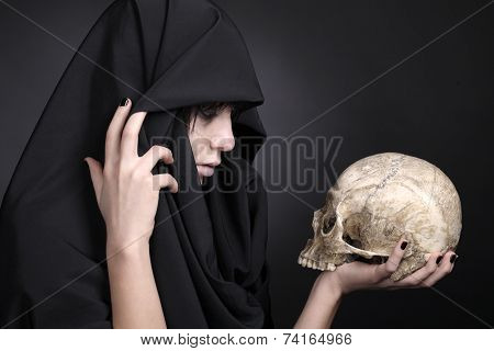 Woman holding a human cranium. Covered with black cloth.
