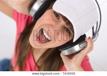 Female Teenager Singing With Headphones