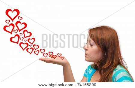 Young woman blowing hearts isolated on white background