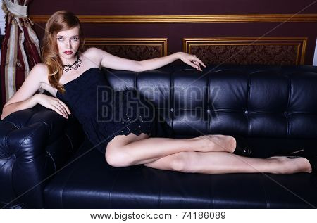 Sexy Woman With Red Hair And Freckles Posing On Black Leather Divan