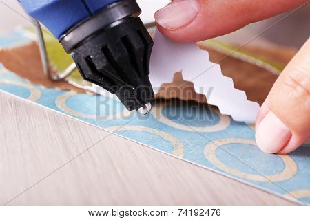 Woman's hand making postcard with a help of glue gun