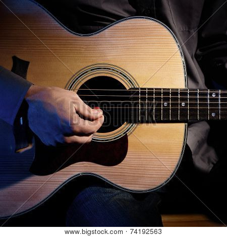 Guitarist playing acoustic guitar. Unplugged performance.