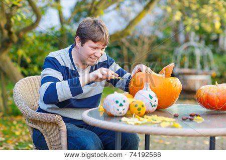 Young Man Hollowing Out A Pumpkin To Prepare Halloween Lantern