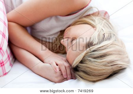 Blond Young Woman Sleeping On A Bed
