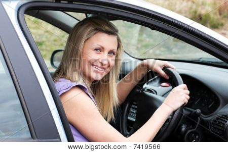Happy Female Driver At The Wheel Sitting In Her Car