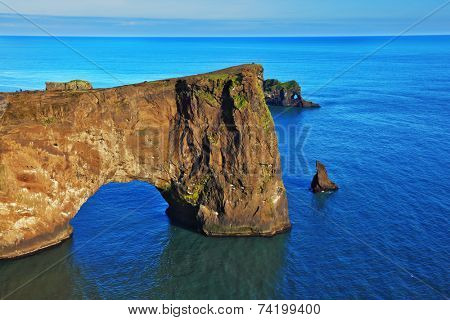 Colossal rock- elephant lit sunset. Cape Dirholaey in southern Iceland in July.