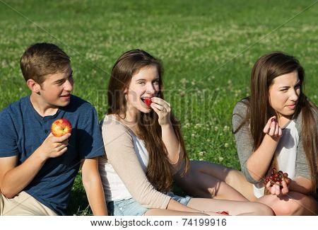 Three Teens Eating Fruit