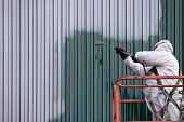 picture of paint spray  - A commercial painter on an industrial lift spray painting a steel exterior wall or duct - JPG