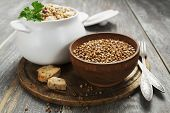 foto of porridge  - Buckwheat porridge with meat in a ceramic pot on the table - JPG