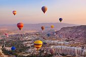 stock photo of valley fire  - Hot air balloon flying over rock landscape at Cappadocia Turkey - JPG