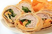 stock photo of sandwich wrap  - A turkey or chicken wrap sandwich with cheddar cheese potato chips - JPG