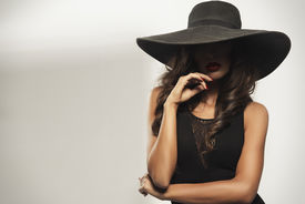 picture of big lips  - Beautiful young woman with red lips wearing summer black hat with large brim - JPG