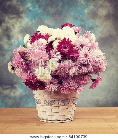 Chrysanthemums In A Basket On A Wooden Table. Vintage Retro Hipster Style Version