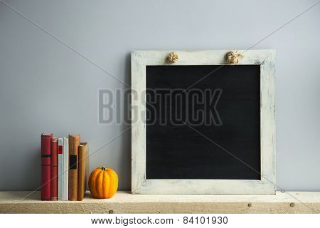 Chalkboard Frame On The Grey Wall With Books And Pumpkin