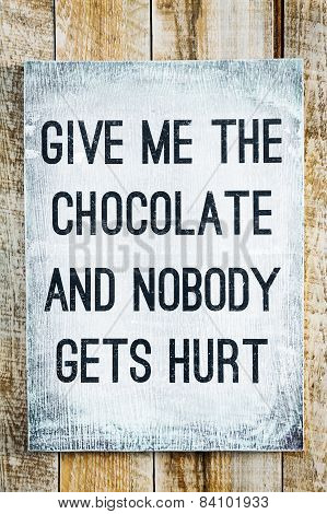 Hipster motivational wooden sign on rustic palette Give me the Chocolate and Nobody gets hurt.