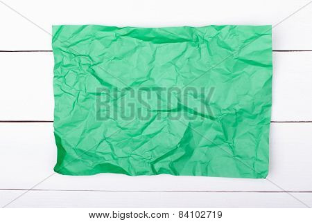 color crumpled paper on white wooden background.