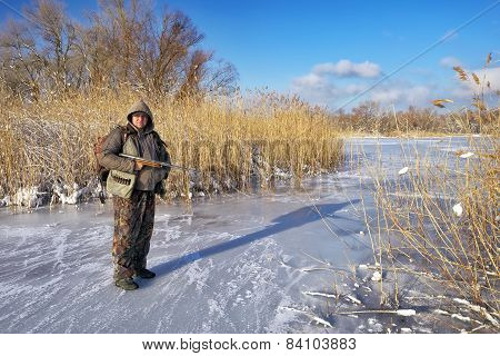 Hunter On The Ice Pond Waiting Victim. Hunter Fully Prepared. Winter Hunting.