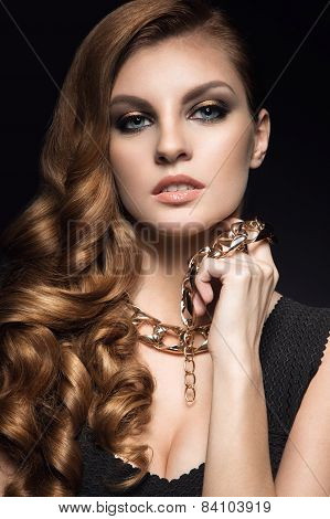 Beautiful brunette woman with perfect skin, bright makeup and gold jewelry. Beauty face.