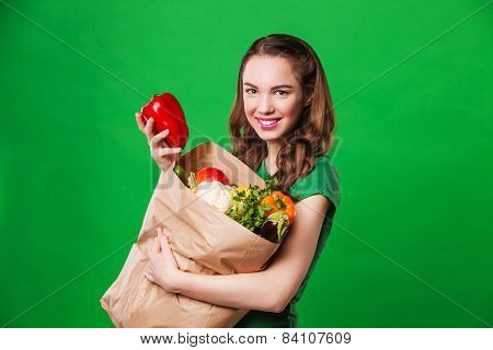 beautiful smiling woman holding a grocery bag full of fresh and healthy food. on green background