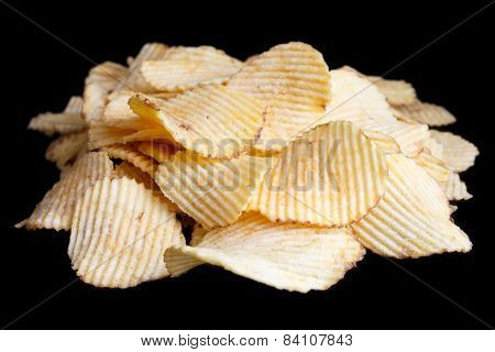 Ridged fried potato crisps on black.