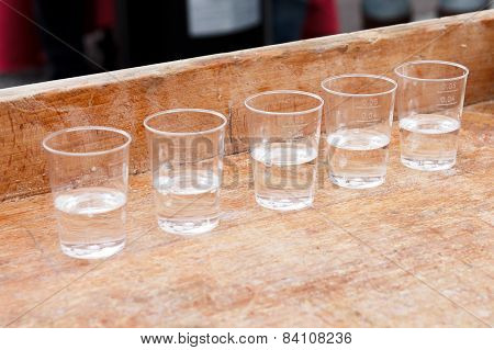 Row of shot glasses with vodka on wooden board