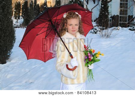 Young blonde bride posing for the camera with red umbrella