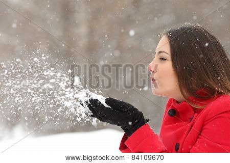 Candid Woman In Red Blowing Snow In Winter