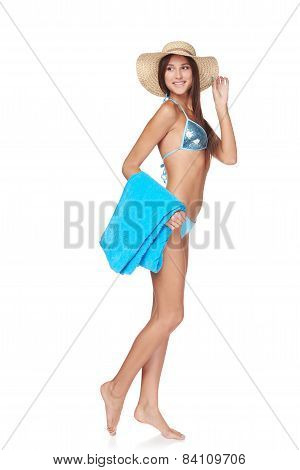 Full length woman in blue bikini with beach towel
