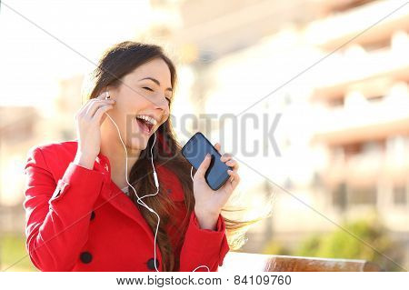 Funny Girl Listening To The Music With Earphones From A Phone