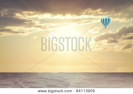 Evening sunset. Concrete floor on background of clouds, sun with air balloon