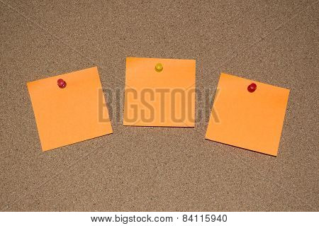 Orange Post it Notes on a Cork Board