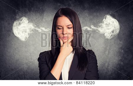 Thoughtful woman with steam from ears. Concrete gray as backdrop