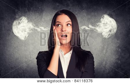 Surprised woman with steam from ears. Concrete gray as backdrop