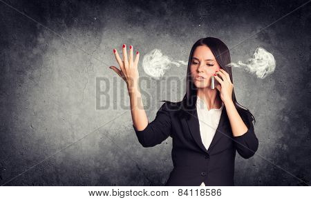 Expressive woman with steam from ears, talking on phone. Concrete gray as backdrop