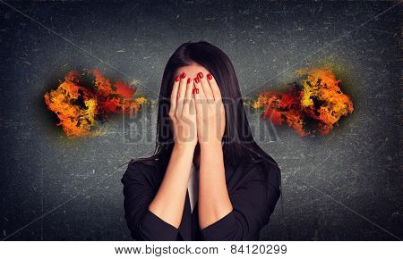 Crying woman with fire from ears. Concrete gray wall as backdrop