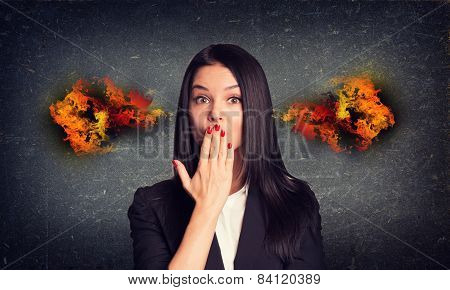 Kissing woman with fire from ears. Concrete gray wall as backdrop