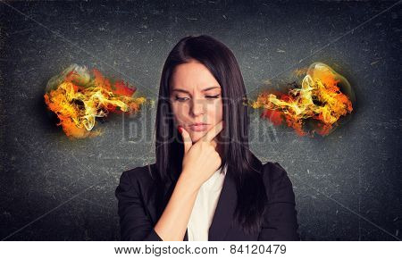 Thoughtful woman with fire from ears. Concrete gray wall as backdrop