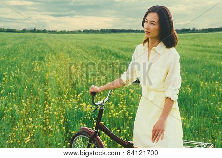 Beautiful woman resting with a bicycle in summer