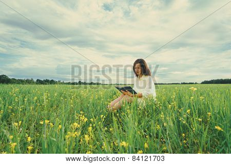 Girl Reading A Book On Summer Meadow