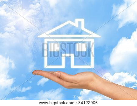 House icon on hand. Background of sky , clouds and sun
