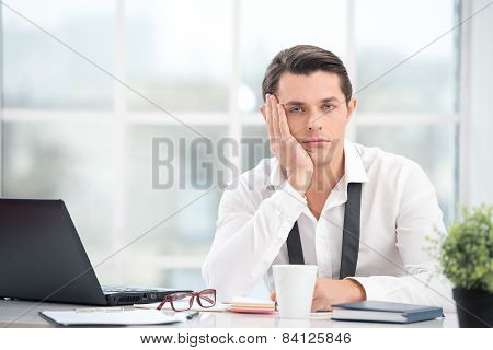 Businessman is bored while working with computer