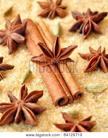 Spices cinnamon sticks,  cardamon and anise over heap of brown sugar