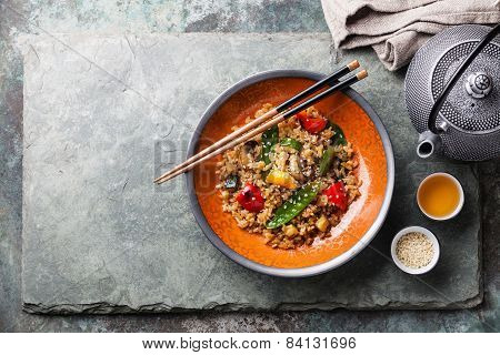 Fried Rice With Vegetables In Red Bowl And Green Tea On Stone Slate Background
