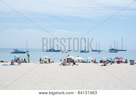 Beach scene with tourists and sunbathers