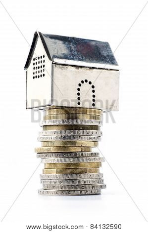 Metallic Model House On A Pile Of Coins, Isolated On White