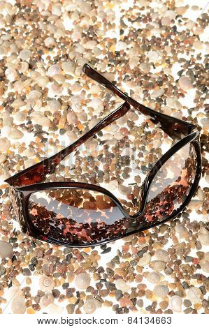 Sunglasses, lying on a white background disintegrating pebbles and sea shell beach