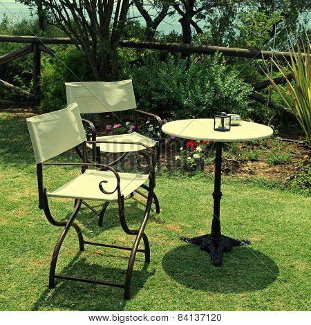 Table and iron chairs on green grass in the garden