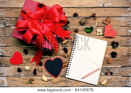 Blank Notebook With Red Gift Box On Wooden Table And Dried Flower